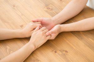 手のアッ。手を握り励ます様子