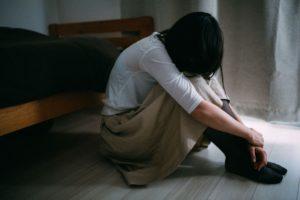 暗い部屋で1人で泣く女性の写真