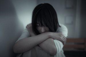 膝を抱えてうつむく女性の写真
