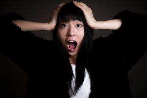 頭を押さえて絶叫する女性の写真
