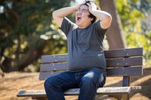 ベンチに座って頭を抱えて絶叫する男性の写真